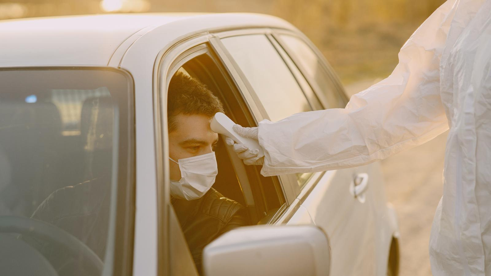 Image of man getting temperature checked with mask on