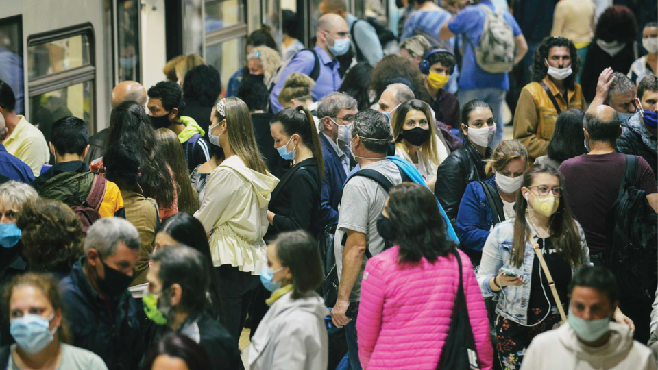 People with masks on waiting for a train