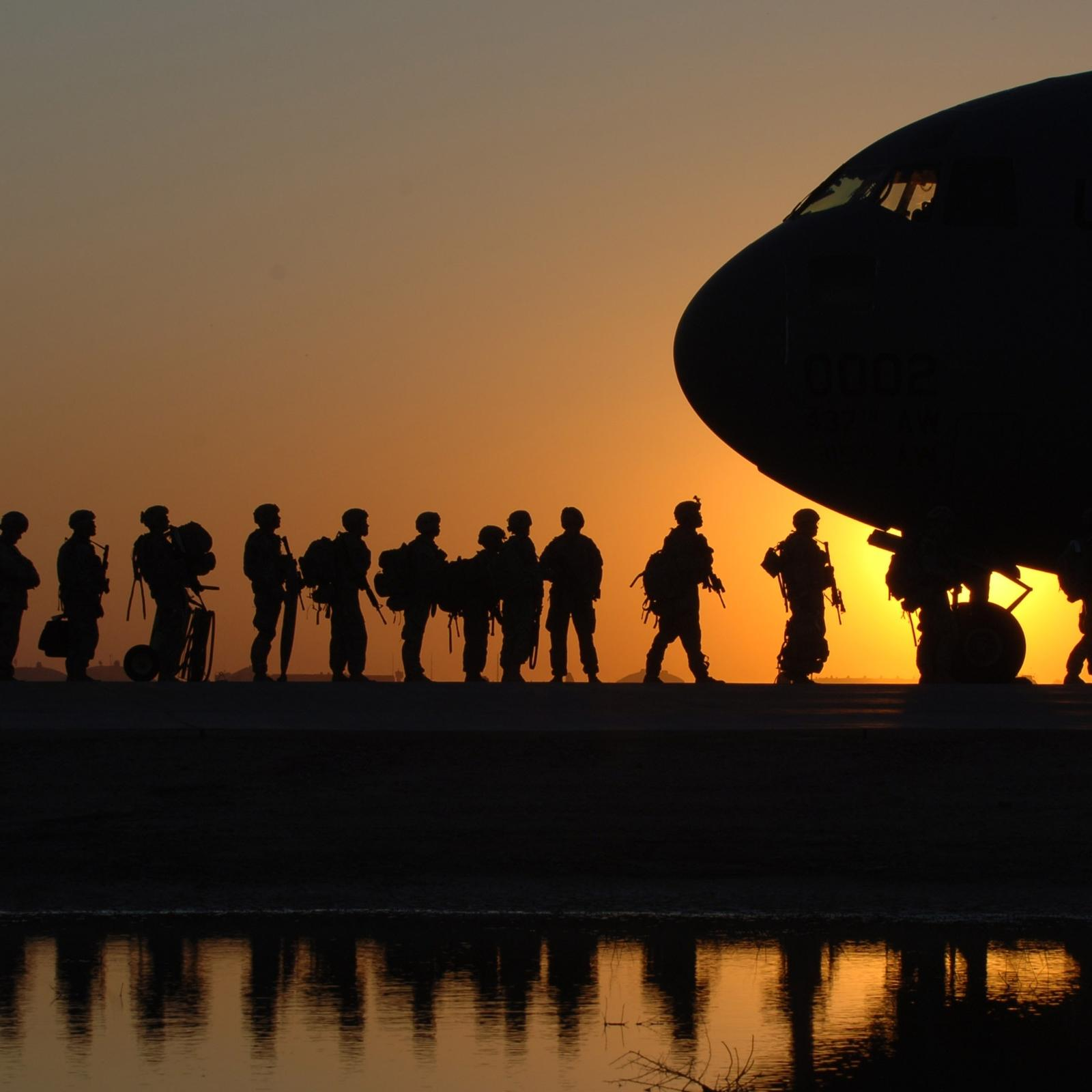 Soldiers silhouettes getting on plane
