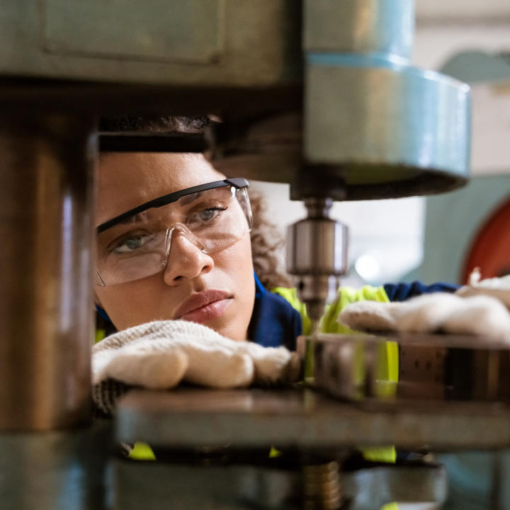 Woman with safety glasses working on machinery