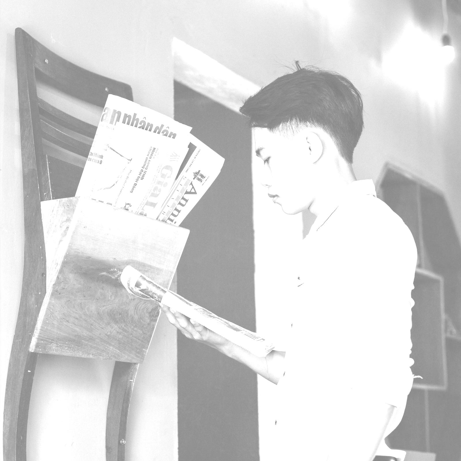 Young man reading newspaper.